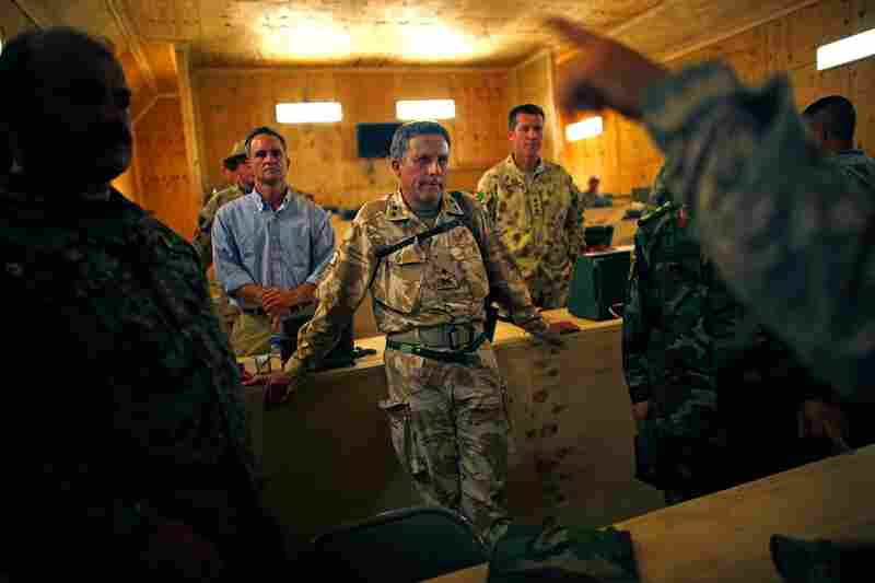 At Forward Operating Base Wilson, British Maj. Gen. Nick Carter (center) explains that to win in Kandahar, the allies must root out the Taliban in  Zhari.