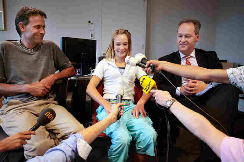 Laura Dekker, just before her 14th birthday in 2009, sits between her father, Dick Dekker (left), and her lawyer Peter de Lange during a courtroom news conference in Utrecht, Netherlands. Dutch courts and social services challenged her parents' consent to allow their daughter to attempt to break the record for youngest solo sail around the world. By December, Dekker had been given permission to...