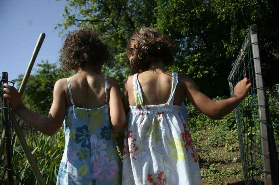 Veda and Annie, twin daughters of NPR producer Justine Kenin, survey their work at the entrance of the Friendship Community Garden, in Washington, D.C. After learning about the White House vegetable garden, the girls wanted a garden of their own, even though they live in a city apartment.