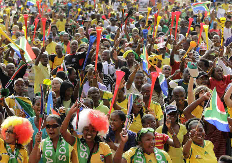 Soccer fans hold up their vuvuzelas as they watch the opening ceremony.