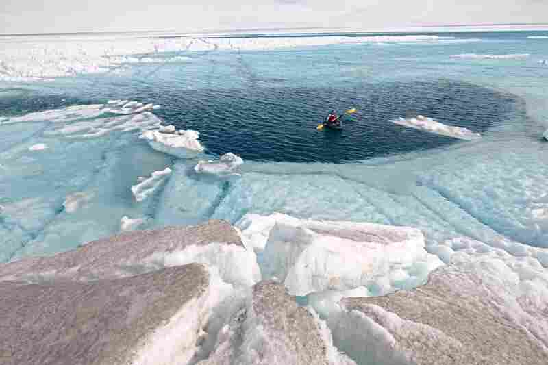 Author Mark Jenkins skims over a moulin 96 feet deep in a meltwater lake. Cryoconite dust scattered on the surrounding ice will likely converge into a darker patch, creating another hot spot for ice loss.