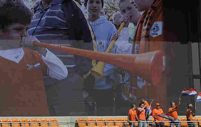 Dutch fans cheer in front of a giant screen showing more fans blowing vuvuzelas prior to the Group E soccer match between the Netherlands and Denmark.