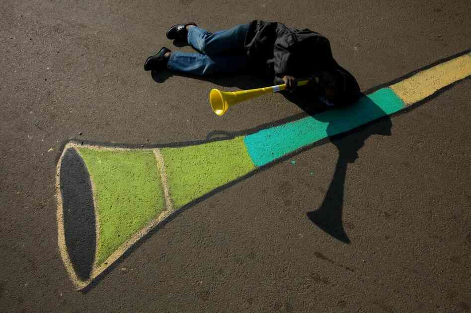A boy in Soweto blows a vuvuzela next to a street painting of the iconic celebratory horn.