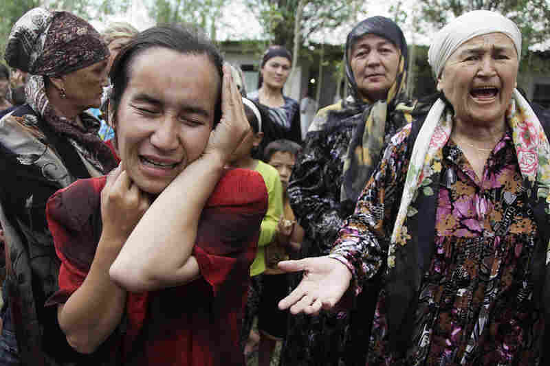 Ethnic Uzbek women, crying, plead for help at a refugee camp in Nariman on the border with Uzbekistan.