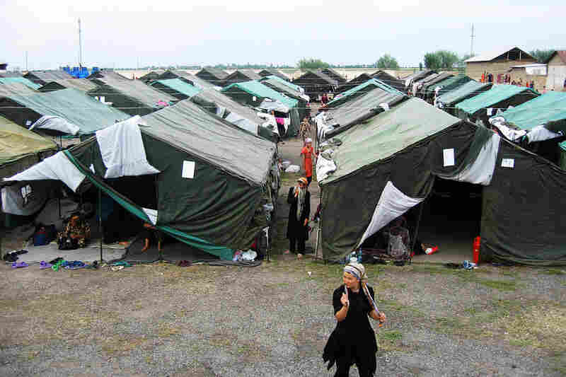 A woman walks in a refugee camp in Yorkishlok on the border between Kyrgyzstan and Uzbekistan. Thousands of ethnic Uzbek refugees remain stranded in Kyrgyzstan, unable to enter Uzbekistan and unwilling to return to their homes in Kyrgyzstan after days of deadly conflict raging across the south of the ex-Soviet state.