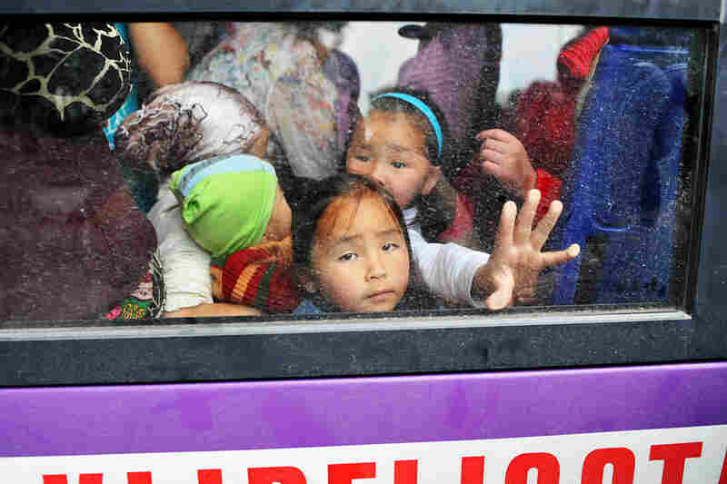 Kyrgyz children look out the window of a Bishkek-bound bus before it departs from Osh.