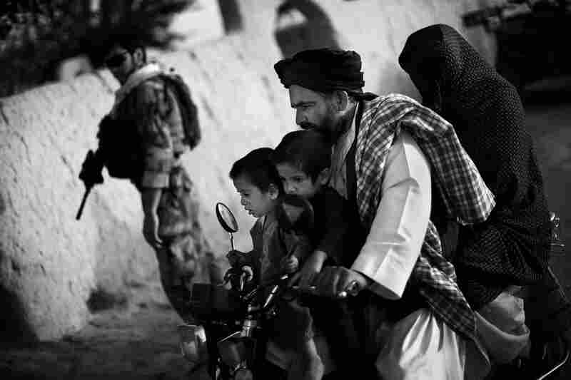 An Afghan family rides past a joint U.S.-Afghan patrol in Ezabad. Special forces aim to train communities to protect themselves. But they must first gain the trust of local Afghans, and overcome the mistrust caused by local police corruption.