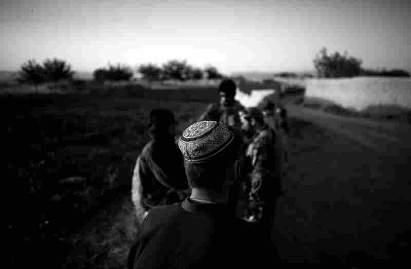 American and Afghan forces stop to talk with villagers on the road outside Ezabad.