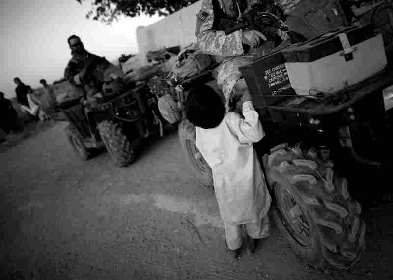 A child approaches Green Berets on patrol in Ezabad. Special Forces use ATVs (or all-terrain vehicles) for better mobility across rough terrain and narrow village roads.