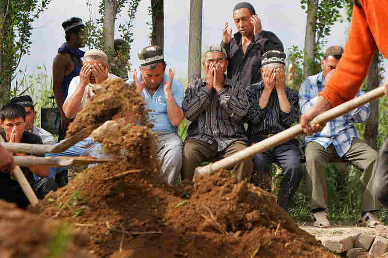 Uzbek men pray during the funeral of a victim who was killed during the riots in Osh.
