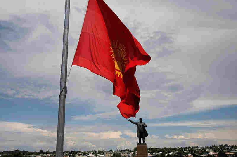 The Kyrgyz national flag flies at half-staff in front of the statue of Vladimir Lenin in a central square in Osh, Kyrgyzstan, on June 16, marking the third national day of mourning after violence in Osh and Jalal Abad.