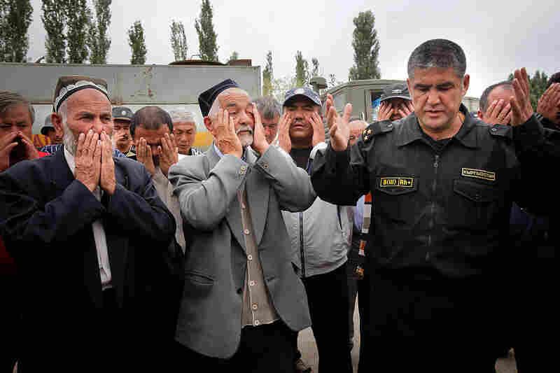 The head of local police, Col. Kursan Asanov (right), leads a prayer for peace after negotiations in which he called on ethnic Uzbeks to pull down a barricade between Uzbek and Kyrgyz districts in Osh.