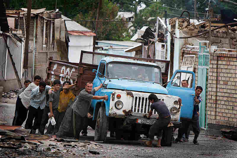 Uzbek men push a truck as they build a barricade in the Uzbek district of Osh.