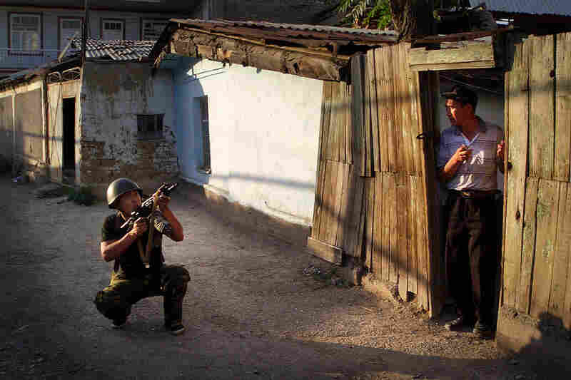 An officer of the Kyrgyz Interior Ministry forces conducts house-to-house searches in the Anoshin neighborhood in Osh.
