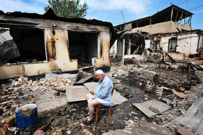 An elderly ethnic Uzbek man sits in front of his burned-out house in Osh on June 15. Uzbekistan closed its border to refugees fleeing the deadly violence in Kyrgyzstan, some of whom have accused government forces of helping armed gangs slaughter ethnic Uzbeks.