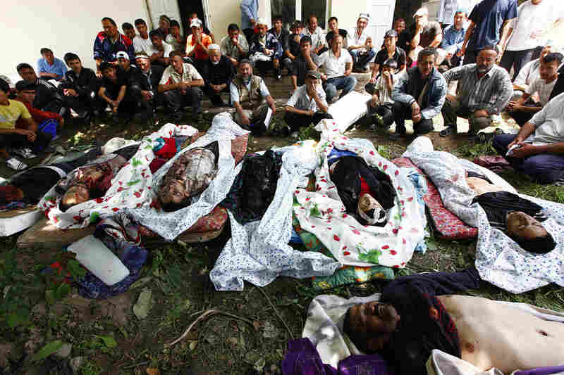 Uzbek residents sit in front of the bodies of victims on June 13. The Kyrgyz government put the death toll from the violence at 117, but officials in neighboring Uzbekistan say the actual number is much higher.