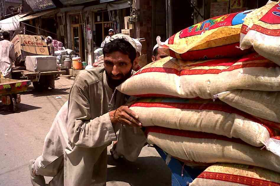 """A man pushes a cart laden with sacks of grain through the streets of Swat Valley's main city Mingora. The Taliban terrorized the population and forced women to stay inside. Now, the markets are teaming again, just one block from the infamous intersection known as """"Bloody Square,"""" where the Taliban carried out public executions."""