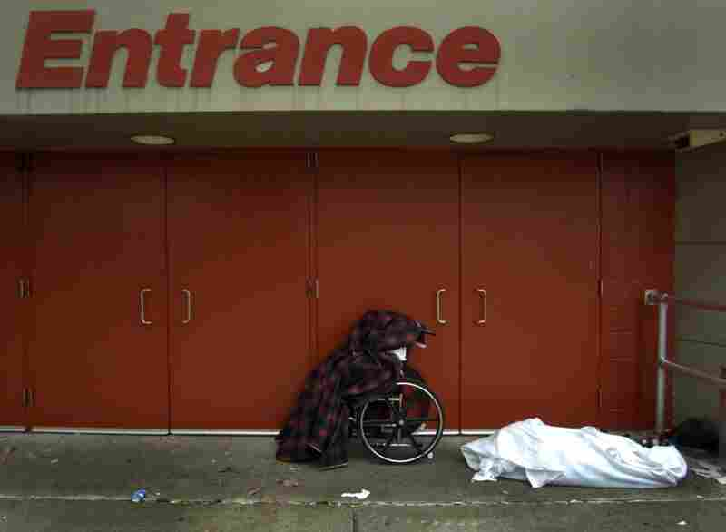 The body of Ethel Freeman, center in wheelchair, and another body lie covered outside an entrance to the Morial Convention Center in New Orleans following Hurricane Katrina. Evacuees showed respect for the dead by draping them with blankets.