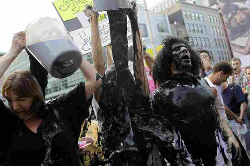 Protesters cover themselves with a water and paint mixture during a demonstration at a BP gas station in New York City on May 28.