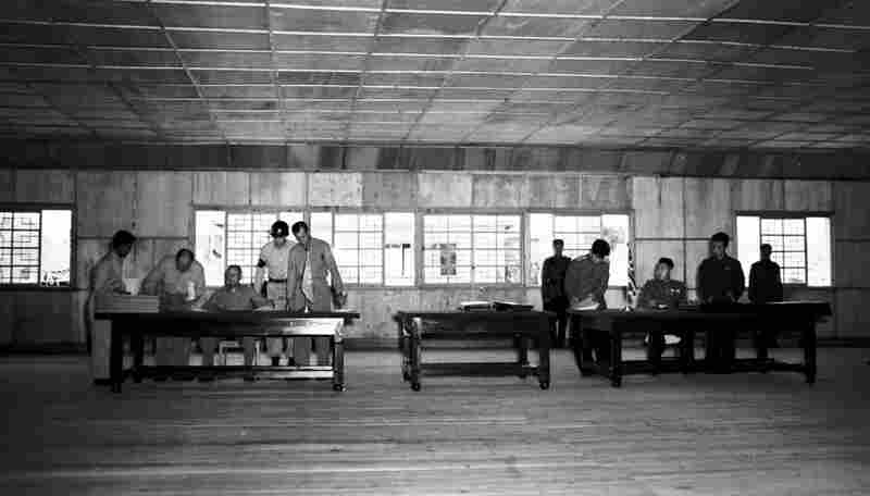 Gen. William K. Harrison, Jr., seated at left, and North Korean Gen. Nam Il, seated at right, sign armistice documents in Armistice Hall in Panmunjom, a no man's land between the Koreas, on July 26, 1953.