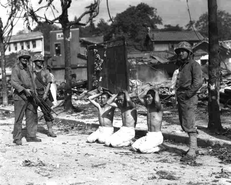 U.S. Marines guard three captured North Koreans.