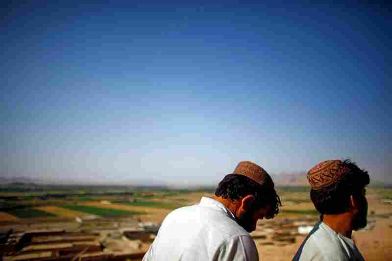 Locals stand on a hill overlooking their neighborhood on the edge of Kandahar city, near the Arghandab valley. Insurgents have used the area to move in and out of the city, making it a difficult region to police.