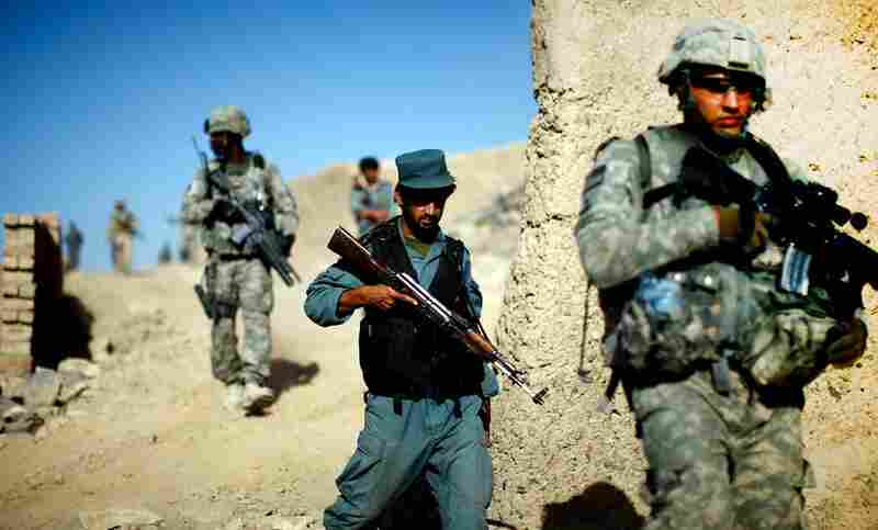 Afghan national police and U.S. soldiers on a joint patrol in a neighborhood on the outskirts of Kandahar city. The U.S. strategy in Afghanistan depends on training and equipping the Afghan security forces, making them self-reliant and allowing U.S. troops to withdraw.