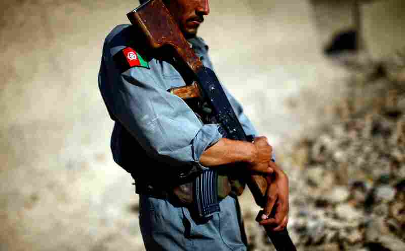 An Afghan national policeman holds his weapon during a patrol. Shah, the commander, says most criminals who are arrested by his police are often released by politicians or judges because of Taliban intimidation.