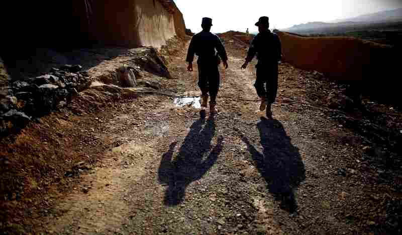 Two Afghan national policemen walk together during a patrol with U.S. soldiers. The consensus is that it will be a long time before complete control can be handed back to the Afghans.