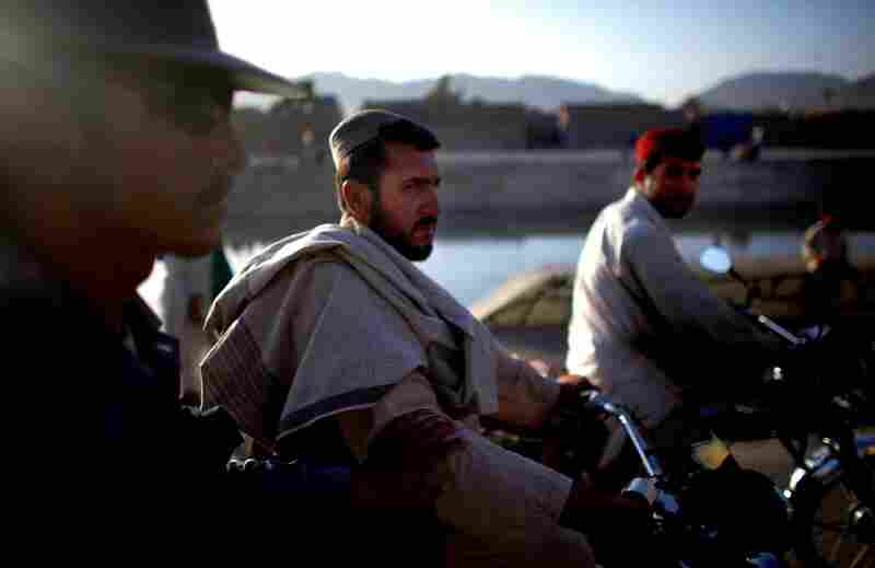 Afghan national police on patrol along a canal near downtown Kandahar. The Afghan government has increased pay, but too many police are still leaving for higher-paying jobs.