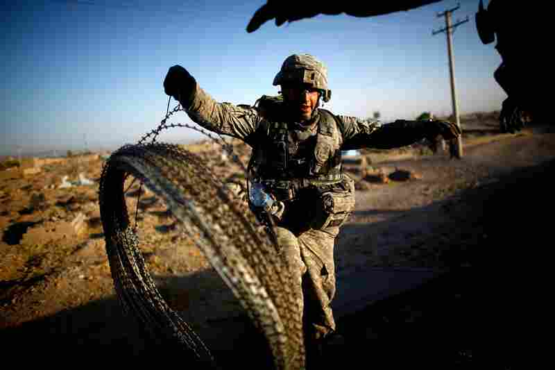U.S. soldiers move a bundle of concertina wire near the base in Kandahar. In the past two years, about 50 percent of the Kandahar city police officers quit, some after just a few months.
