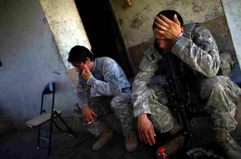 U.S. soldiers from the 97th Military Police Battalion sit in their base, exhausted after a patrol in the heat of the day in Kandahar city.