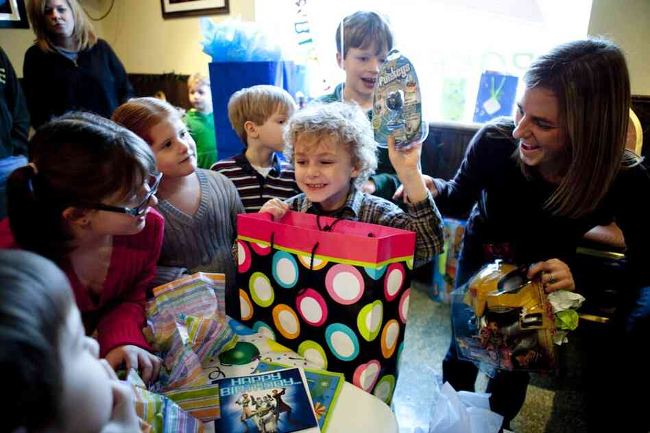 Brianne Zimmerman helps her son, Noah Garland, open presents during his birthday party at Shrewsbury Lanes in St. Louis. She and her husband, Nathan Garland, represent a growing trend of couples who opt to have children without first being married.
