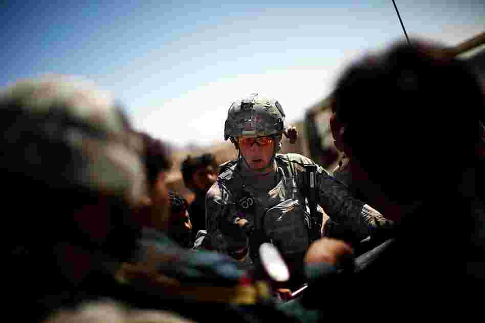 Capt. Nick Stout, commander of Alpha Company, readies his men and Afghan soldiers and police for a joint patrol to pursue the people responsible for throwing hand grenades at his patrols.