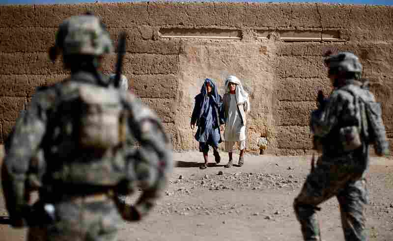Villagers in Sangeray watch soldiers from Alpha Company during the patrol. The dense urban environment makes it easy for Taliban insurgents to throw grenades at the soldiers and disappear into the surroundings.