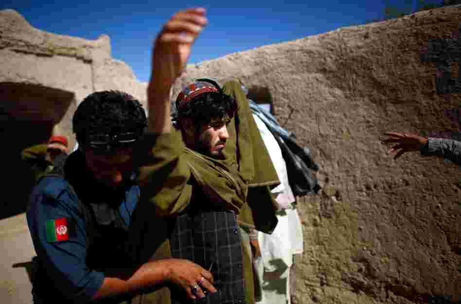 An Afghan national police officer searches a man in Sangeray. The top Taliban leader, Mullah Omar, was born in the Zhari district and many of his first recruits came from here.