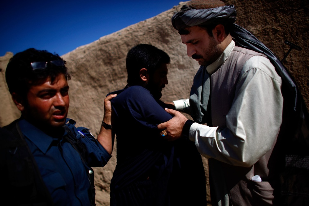 An Afghan national police officer (left) searches a man while Karim Jan (right) holds his arms. The counterinsurgency strategy relies heavily on the police, who live in the community, are closest to the people and should be able to spot insurgents.