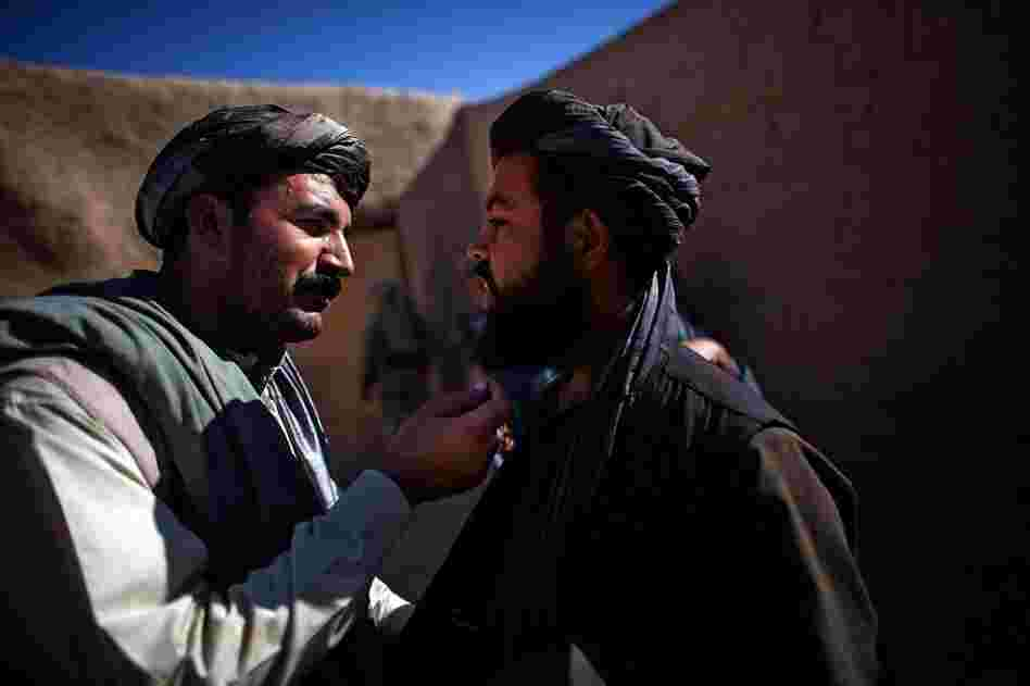 Karim Jan (left) touches the beard of a man he suspects in grenade attacks in the village of Sangeray. The man was arrested after he was questioned. He could not produce a local identity card and was speaking with a foreign accent.