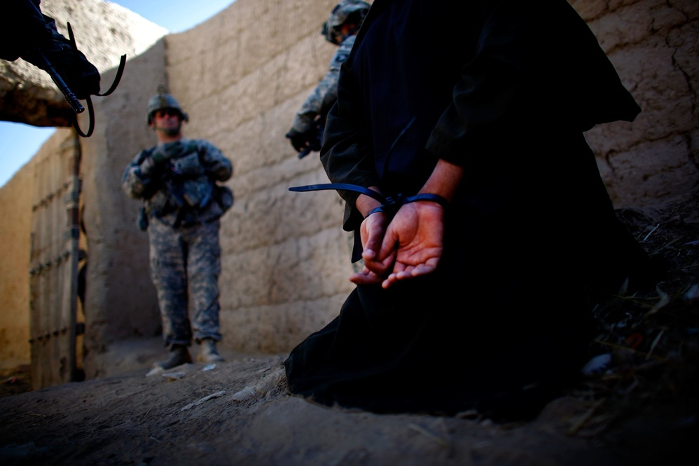 A man suspected of helping the Taliban in grenade attacks is cuffed and detained for further questioning by coalition forces.
