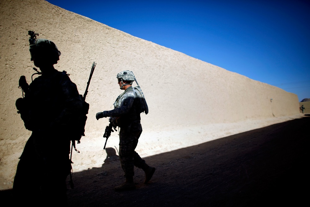Soldiers from Alpha Company walk beneath the high mud walls that make up the labyrinth of alleyways and corridors of the village of Sangeray. In less than a week, five grenade attacks injured more than a half dozen U.S. and Afghan troops.