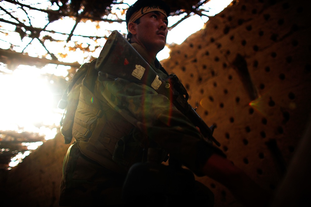 An Afghan National Army soldier walks past a grape-drying barn while looking for sniper hideouts. Buildings in the area are routinely trapped with explosives to be triggered by soldiers. The top Taliban leader, Mullah Omar, was born in the Zhari area, and many of his first recruits came from this region.