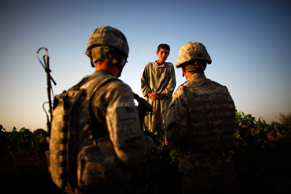 Soldiers with Bravo Company talk to a boy contracted to work in the vineyards. The soldiers are constantly patrolling in an effort to communicate with locals about security in the area.