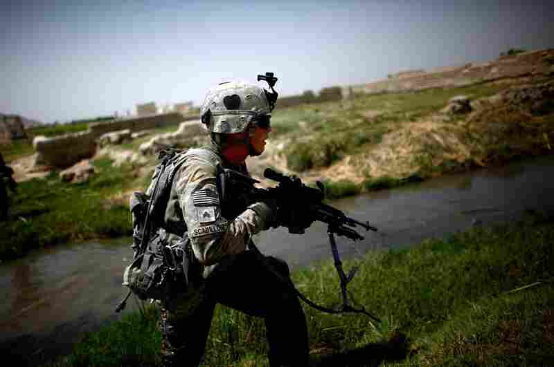 Sgt. Robert Scabilloni runs to take a position while under fire near an irrigation ditch.