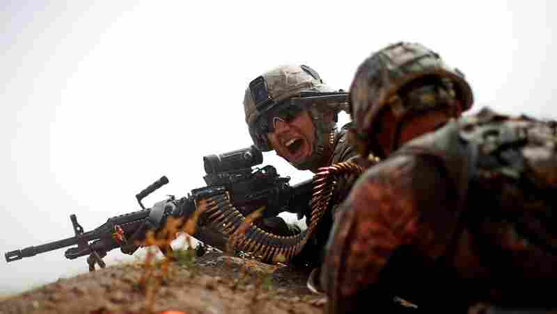 Spc. Jotiyar Saaty yells for more ammunition while combating heavy enemy fire near the village of Payendi. Soldiers from Bravo Company fought a 4-hour running gun battle with insurgents, trading fire with the enemy as the Americans made their way back to their combat outpost.