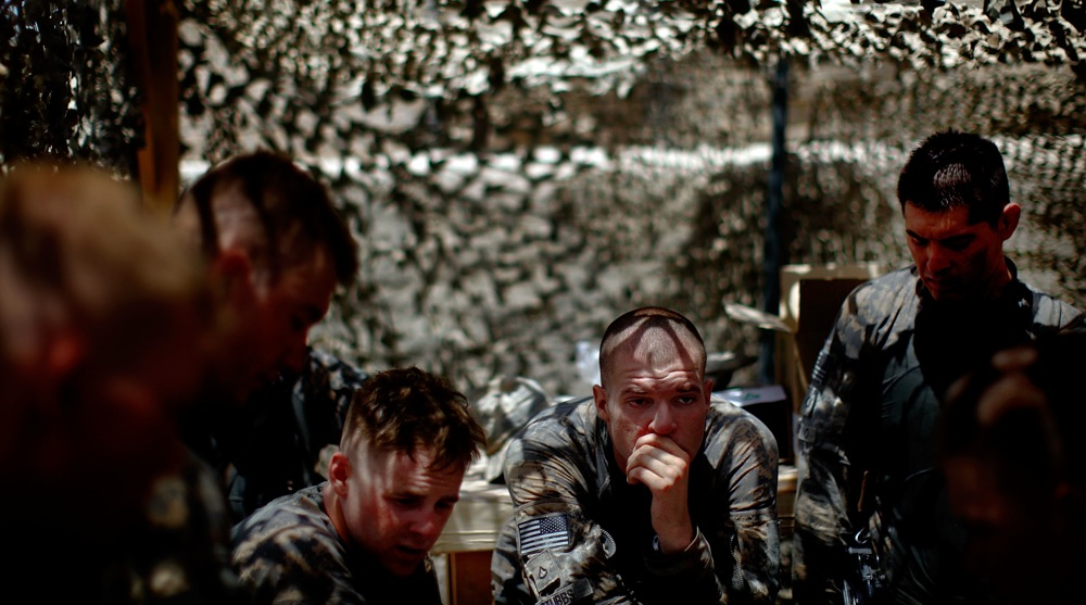 Pfc. Michael Stubbs (center) rests during a debriefing after the intense gun battle with the Taliban.
