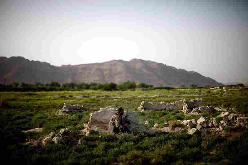 An Afghan soldier on patrol with Bravo Company crouches behind a rock after gunshots are fired.