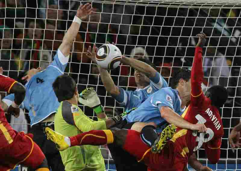 Uruguay's striker Luis Suarez (center) stops the ball with his hands, leading to a red card and a penalty kick for Ghana during quarterfinal action between Uruguay and Ghana.