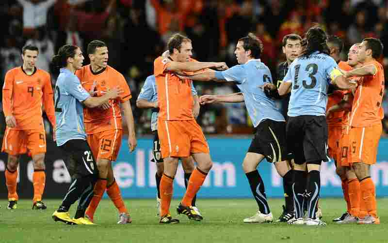 Members of the Uruguay and Netherlands teams, including Netherlands' Joris Mathijsen (center left) and Uruguay's Diego Godin (center right), scuffle at the end of the match.
