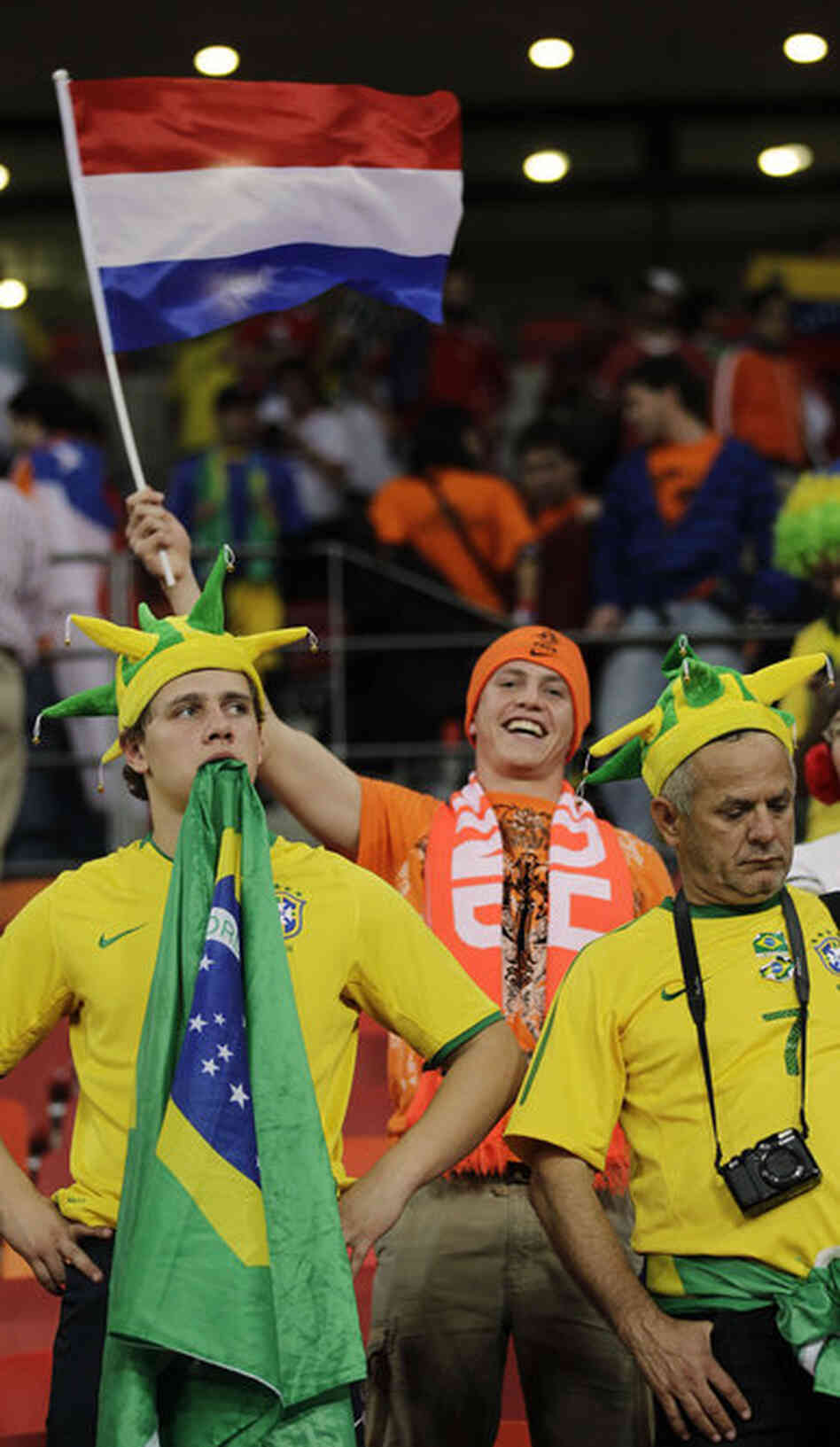 Brazil supporters react as a Netherlands fan celebrates following the quarterfinal match between the Netherlands and Brazil. Netherlands defeated Brazil 2-1.