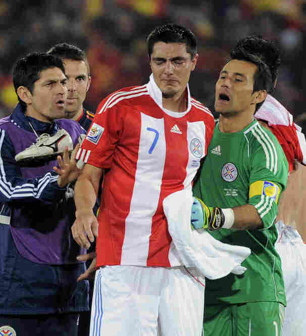 Paraguay's Oscar Cardozo is comforted by goalkeeper Justo Villar (right) following their 1-0 loss to Spain.